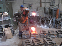 Fence -- Swiss Foundry -- pouring metal for fence elements into molds.