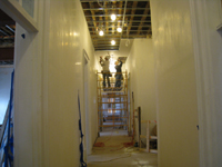 Second Floor--Installing drywall on the ceiling in the central corridor (looking west) - March 15, 2011
